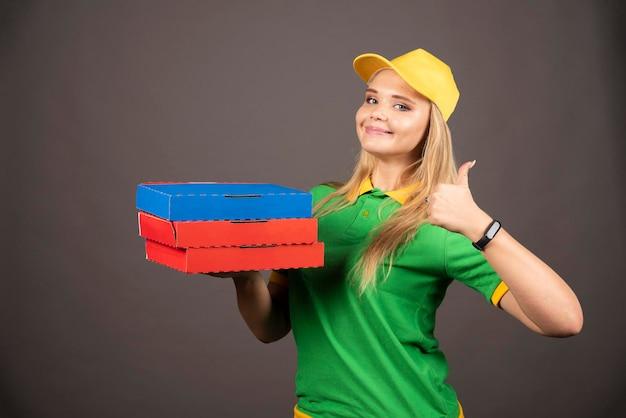 Lieferfrau, die pappkartons der pizza hält und daumen oben zeigt. hochwertiges foto