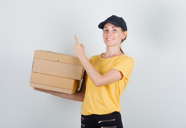 Lieferfrau, die pappkartons mit finger oben im t-shirt, in der hose und in der mütze hält und fröhlich schaut