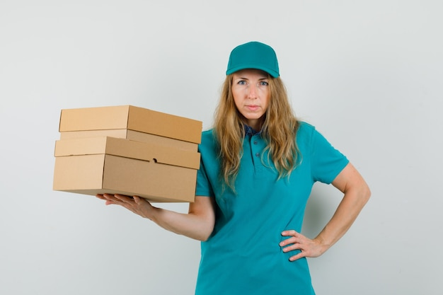 Lieferfrau, die pappkartons mit hand auf taille im t-shirt, kappe hält
