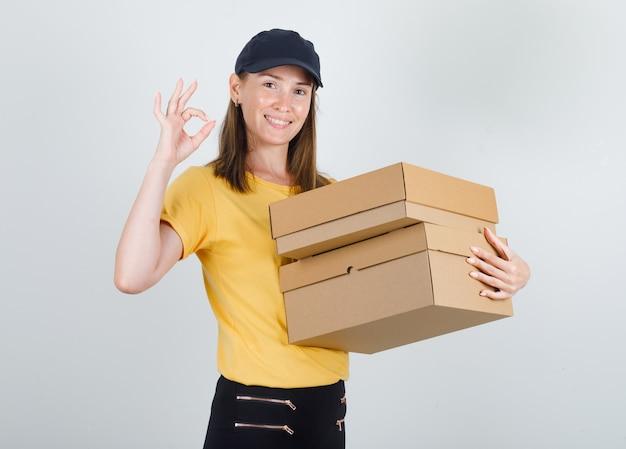 Lieferfrau, die pappkartons mit ok-zeichen im t-shirt hält
