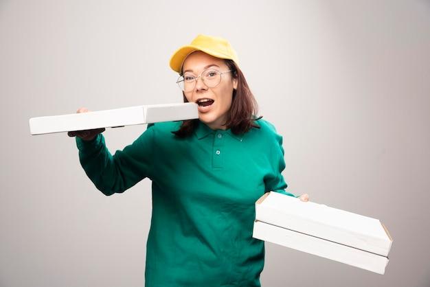 Lieferfrau, die pappkartons pizza auf einem weiß hält. foto in hoher qualität