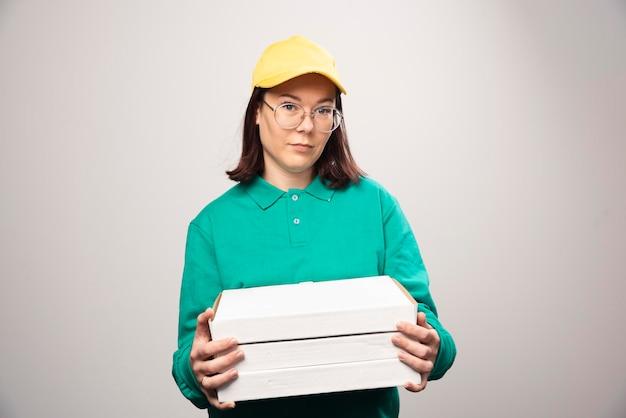 Lieferfrau, die pappkartons pizza auf einem weiß trägt. foto in hoher qualität