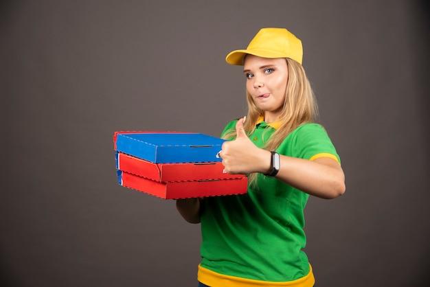 Lieferfrau, die pappkartons pizza hält und daumen nach oben zeigt.
