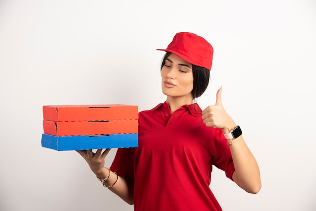 Lieferfrau, die pizza über weißem hintergrund hält, der daumen hoch geste gibt.