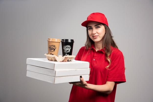 Lieferfrau, die pizza und kaffeetassen an grauer wand hält.