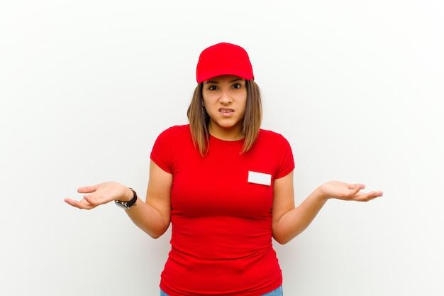 Lieferfrau, die sich ahnungslos und verwirrt fühlt, nicht sicher ist, welche wahl oder option sie wählen soll und sich gegen weiß wundert
