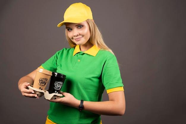 Lieferfrau, die tassen kaffee auf dunklem hintergrund hält. hochwertiges foto