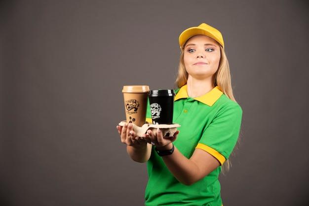 Lieferfrau, die tassen kaffee auf schwarzer wand gibt.