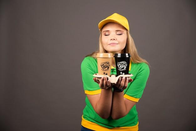 Lieferfrau, die tassen kaffee auf schwarzer wand hält.