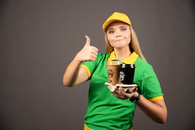 Lieferfrau, die tassen kaffee hält und sich daumen zeigt.
