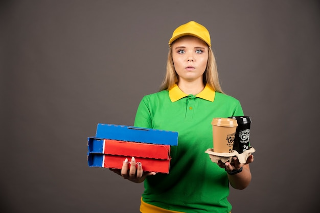 Lieferfrau, die tassen kaffee und pappkartons pizza hält.