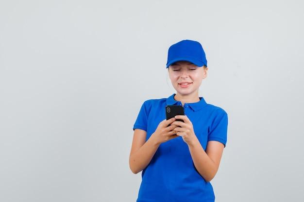 Lieferfrau, die text-chat auf handy in blauem t-shirt und mütze hat und fröhlich schaut