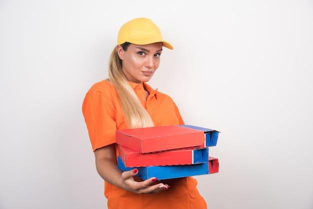 Lieferfrau, die vorne schaut und pizzaschachteln auf weißem raum hält