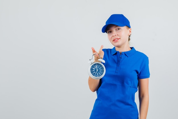 Lieferfrau, die wecker hält und im blauen t-shirt und in der kappe lächelt