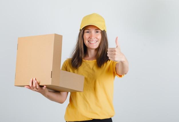 Lieferfrau hält geöffnete schachtel mit daumen nach oben in gelbem t-shirt, hose, mütze und sieht fröhlich aus