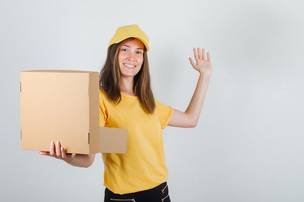 Lieferfrau hält geöffnete schachtel mit handzeichen in t-shirt, hose, mütze und sieht froh aus