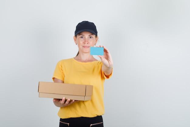Lieferfrau hält pappkarton und blaue karte in t-shirt, hose und mütze