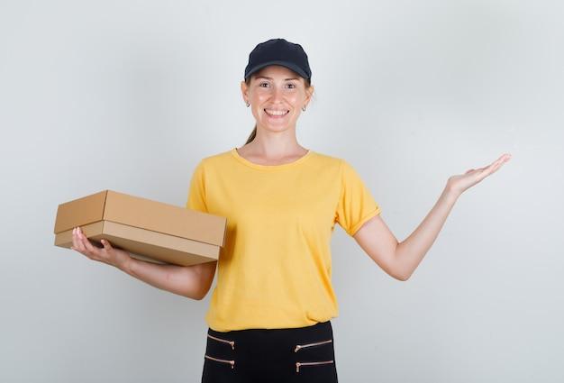 Lieferfrau hält pappkarton und lächelt in t-shirt, hose und mütze