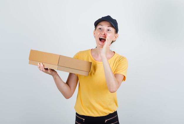 Lieferfrau hält pappkarton und schreit in t-shirt, hose und mütze
