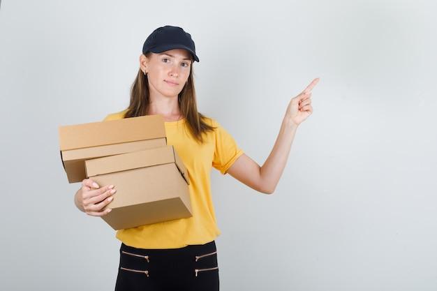 Lieferfrau hält pappkartons mit finger oben in t-shirt, hose und mütze