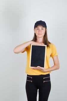 Lieferfrau hält tafel in t-shirt, hose und mütze und sieht froh aus