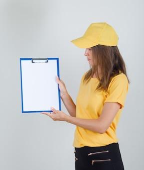Lieferfrau hält und betrachtet zwischenablage in gelbem t-shirt, hose und mütze