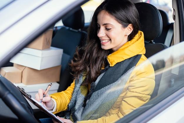 Lieferfrau im auto mit paket