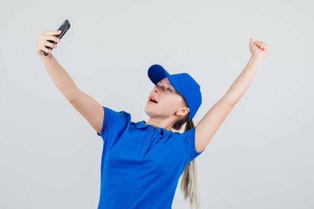 Lieferfrau im blauen t-shirt und in der kappe, die selfie nehmen, während siegergeste zeigen