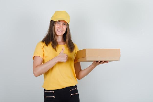 Lieferfrau im gelben t-shirt, in der hose, in der kappe, die pappkarton mit daumen nach oben hält und fröhlich aussieht