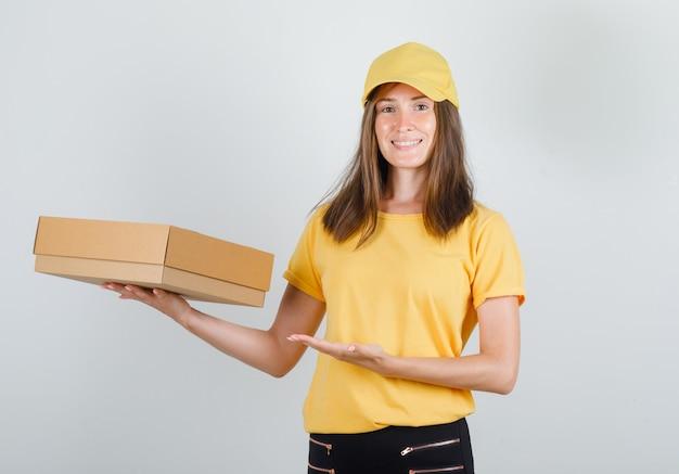 Lieferfrau im gelben t-shirt, in der hose, in der kappe, die pappkarton zeigt und fröhlich schaut