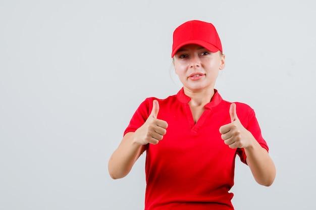 Lieferfrau im roten t-shirt und in der kappe, die daumen hoch zeigt und zufrieden schaut