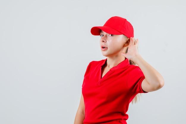 Lieferfrau im roten t-shirt und in der kappe, die hand hinter ohr hält und neugierig schaut