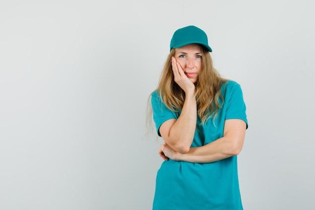 Lieferfrau im t-shirt, mütze, die wange auf erhobene handfläche lehnt und niedlich aussieht