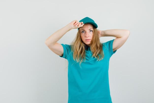 Lieferfrau im t-shirt, mütze posierend, während sie ihre mütze hält