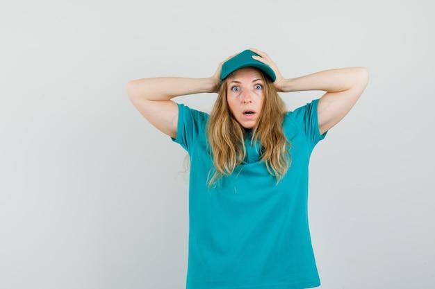 Lieferfrau im t-shirt, mütze umklammert den kopf in den händen und sieht verwirrt aus