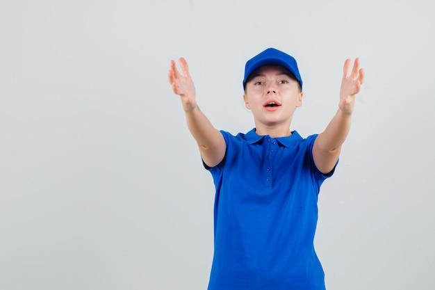 Lieferfrau in blauem t-shirt und mütze streckt die arme wie etwas erhalten