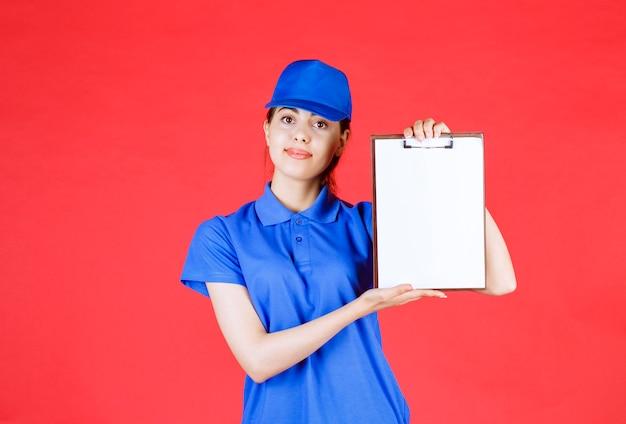 Lieferfrau in blauer ausstattung, die leere zwischenablage auf rot hält.