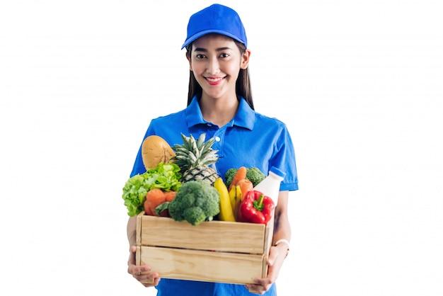 Lieferfrau in der blauen uniform, die paket des lebensmittellebensmittels mit gemüse und obst auf weiß lokalisiert trägt