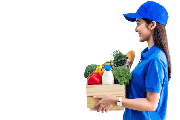 Lieferfrau in der blauen uniform, die paket des lebensmittellebensmittels mit gemüse und obst auf weißem hintergrund trägt