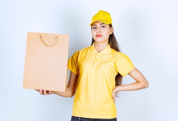 Lieferfrau in der gelben kappe, die braunes kraftpapier hält und auf weiß aufwirft.