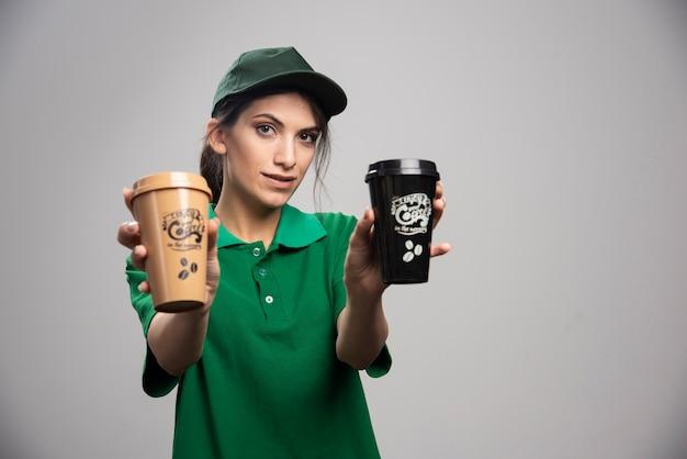 Lieferfrau in der grünen uniform, die mit köstlichem kaffee aufwirft.