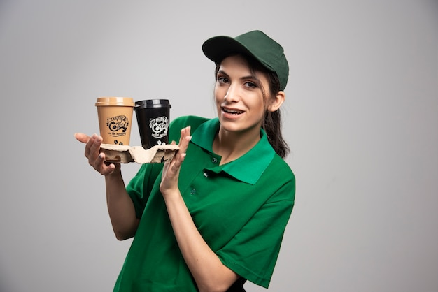 Lieferfrau in der grünen uniform, die mit tassen kaffee aufwirft.
