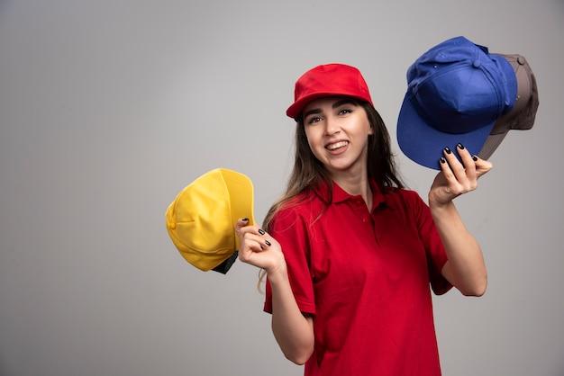 Lieferfrau in der roten uniform, die bunte kappen hält.