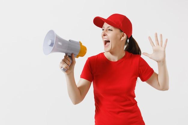 Lieferfrau in der roten uniform lokalisiert auf weißem hintergrund. frau in mütze, t-shirt, die als kurier arbeitet und in megaphon-heißen nachrichten schreit. fun girl kündigt rabattverkauf an. kopieren sie platz für werbung.