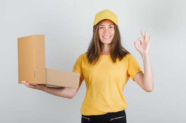 Lieferfrau in gelbem t-shirt, hose, mütze hält geöffnete schachtel mit ok-zeichen und sieht froh aus