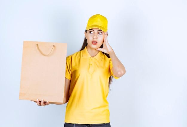 Lieferfrau in gelber mütze, die braunes kraftpapier hält und ihr gesicht hält.