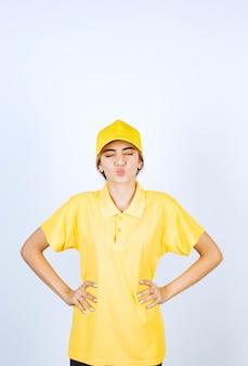 Lieferfrau in gelber uniform, die mit den händen auf den hüften steht und posiert.