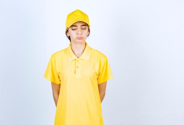 Lieferfrau in gelber uniform, die mit geschlossenen augen gegen weiße wand steht.