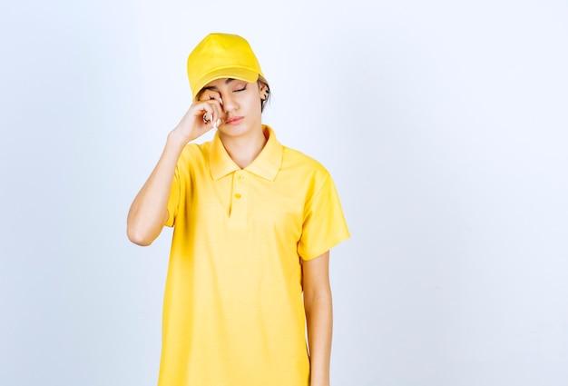Lieferfrau in gelber uniform, die mit schläfrigem gesicht und geschlossenen augen steht.