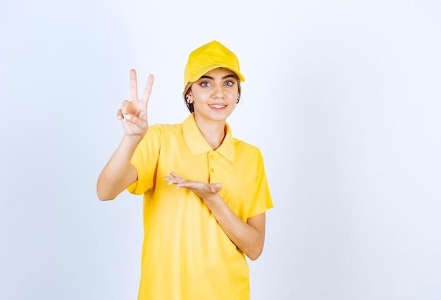 Lieferfrau in gelber uniform, die zwei finger zeigt und victory-zeichen macht.